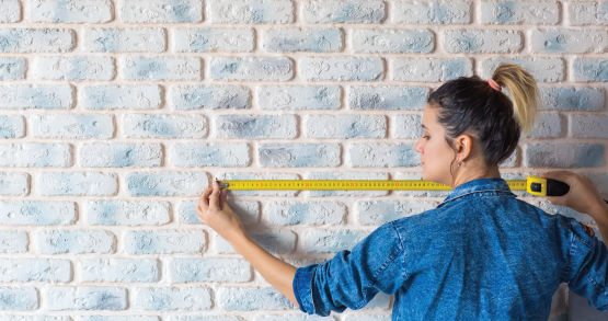 a woman measuring a wall