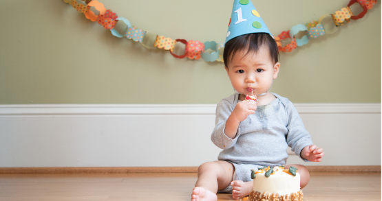 a baby eating cake on his first birthday
